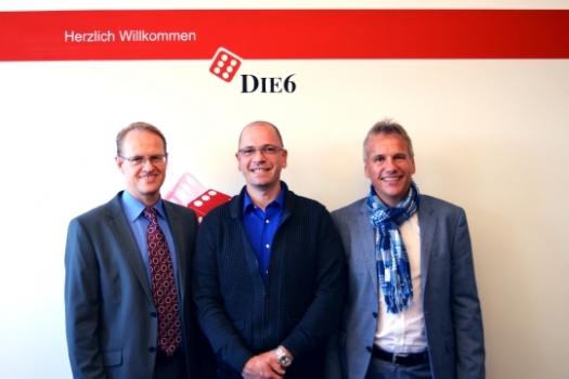 DIE6-Geschäftsführer Holger Kapanski (m) begrüßt die beiden Geschäftsführer des neuen DIE6-Verbundmitglieds Holtzmann Creativ Werbemittel. Jens (r) und Dirk Holtzmann führen das Familienunternehmen in der dritten Generation.